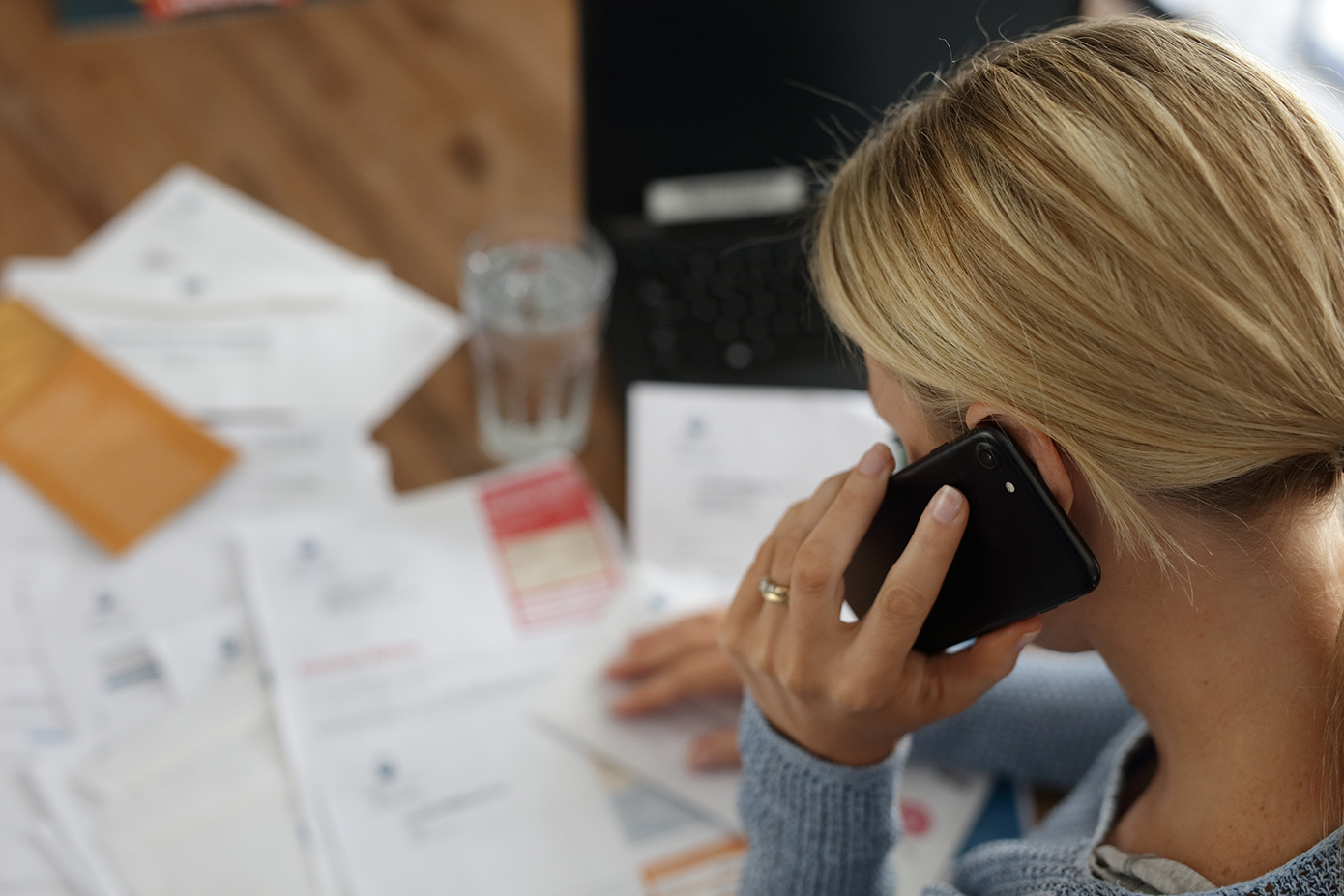 Woman calling on mobile phone while sitting at desk covered with bills