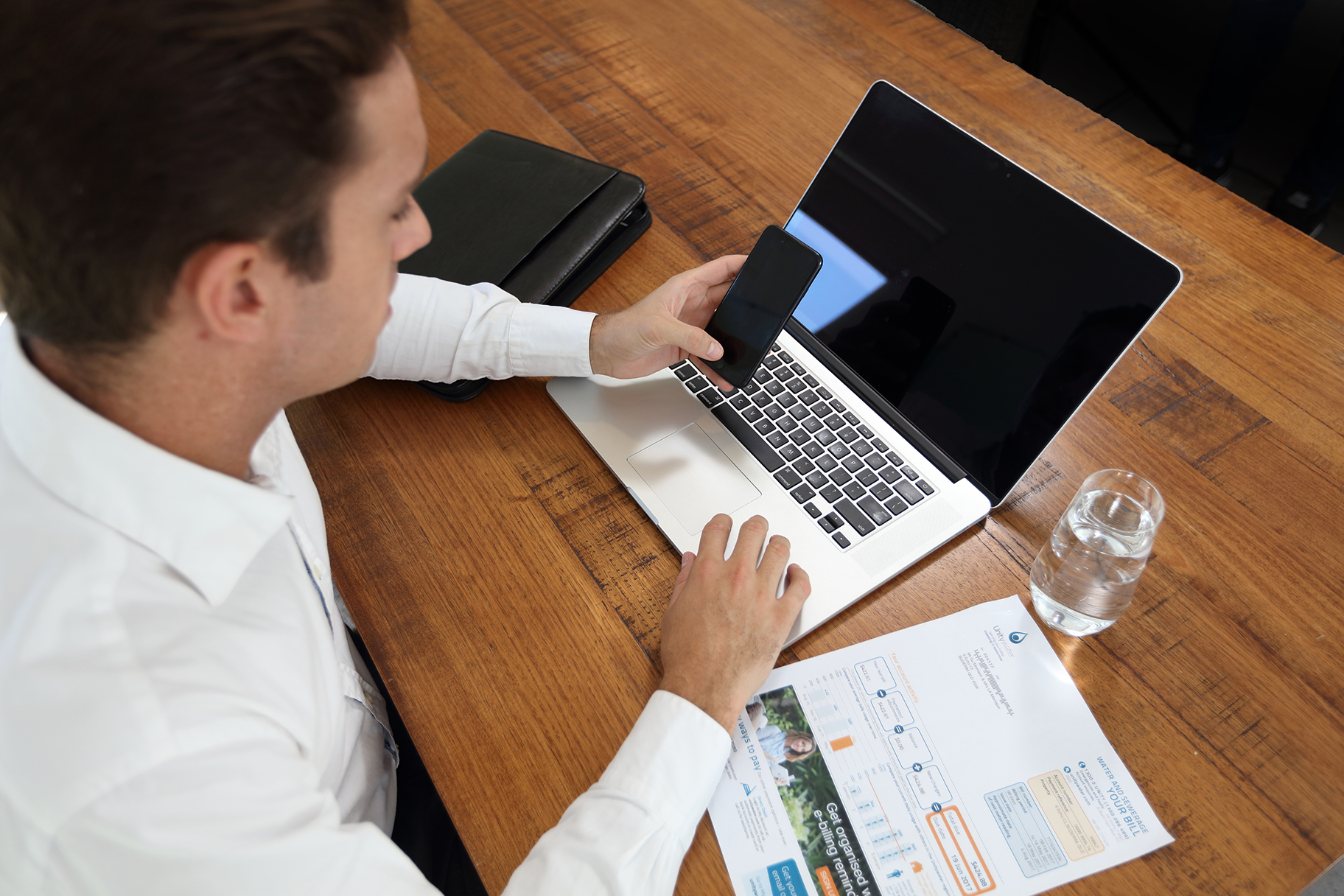 Man looking at mobile phone and laptop computer with Unitywater bill on desk
