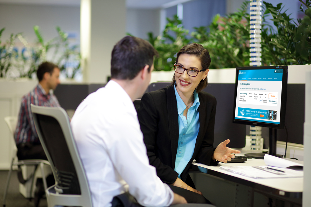 Business woman and man talking in front of desktop computer with My Account on the screen