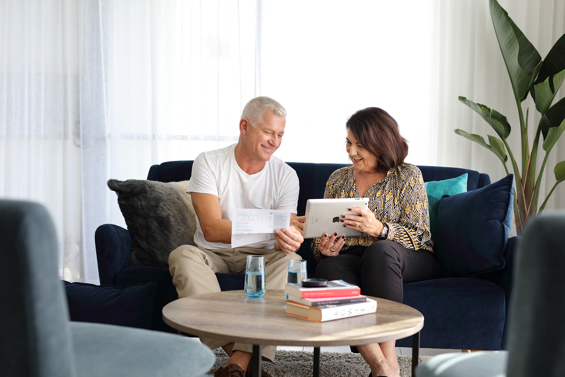 Man and woman looking at bill and tablet on couch