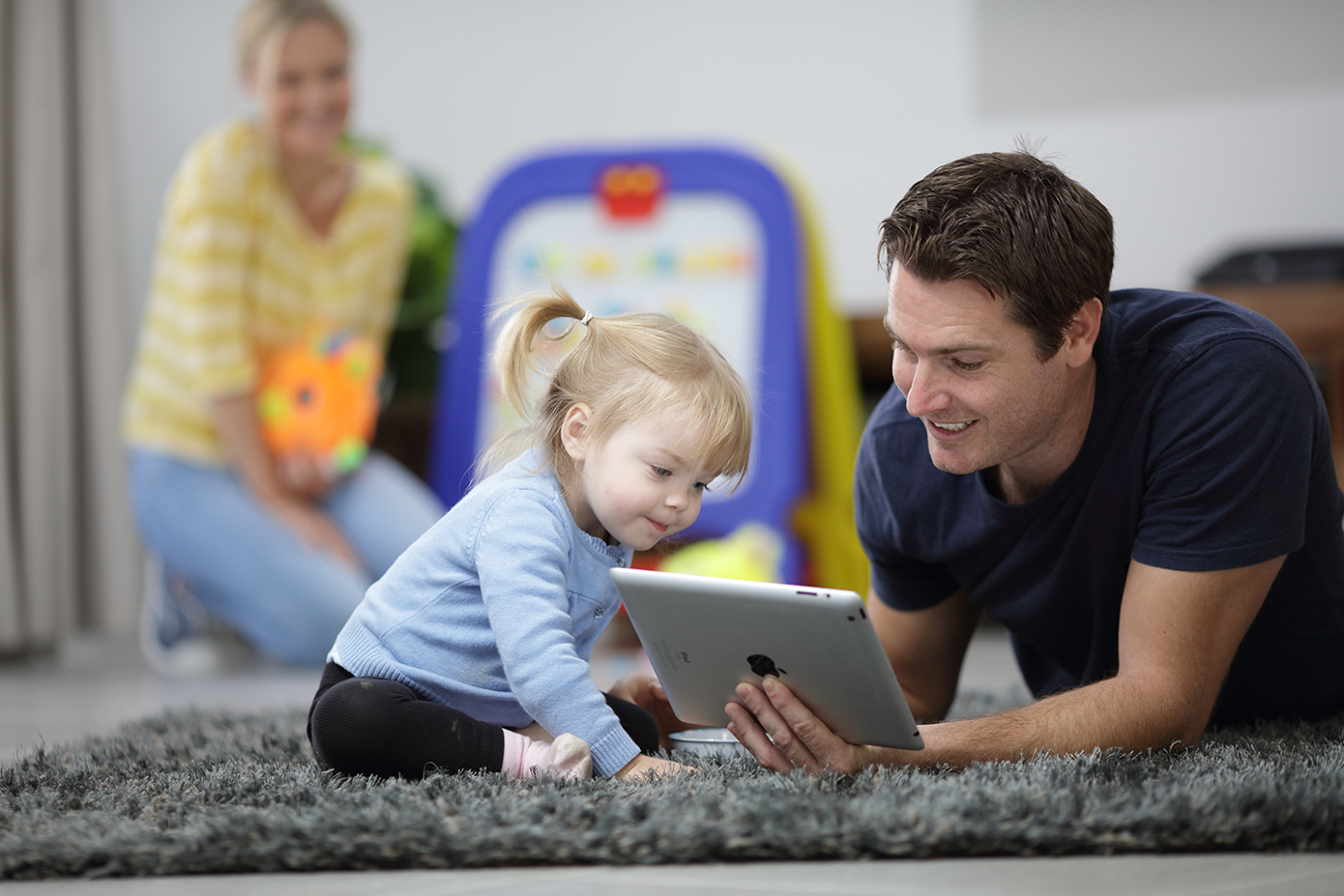 Man and young child in residential home looking at iPad