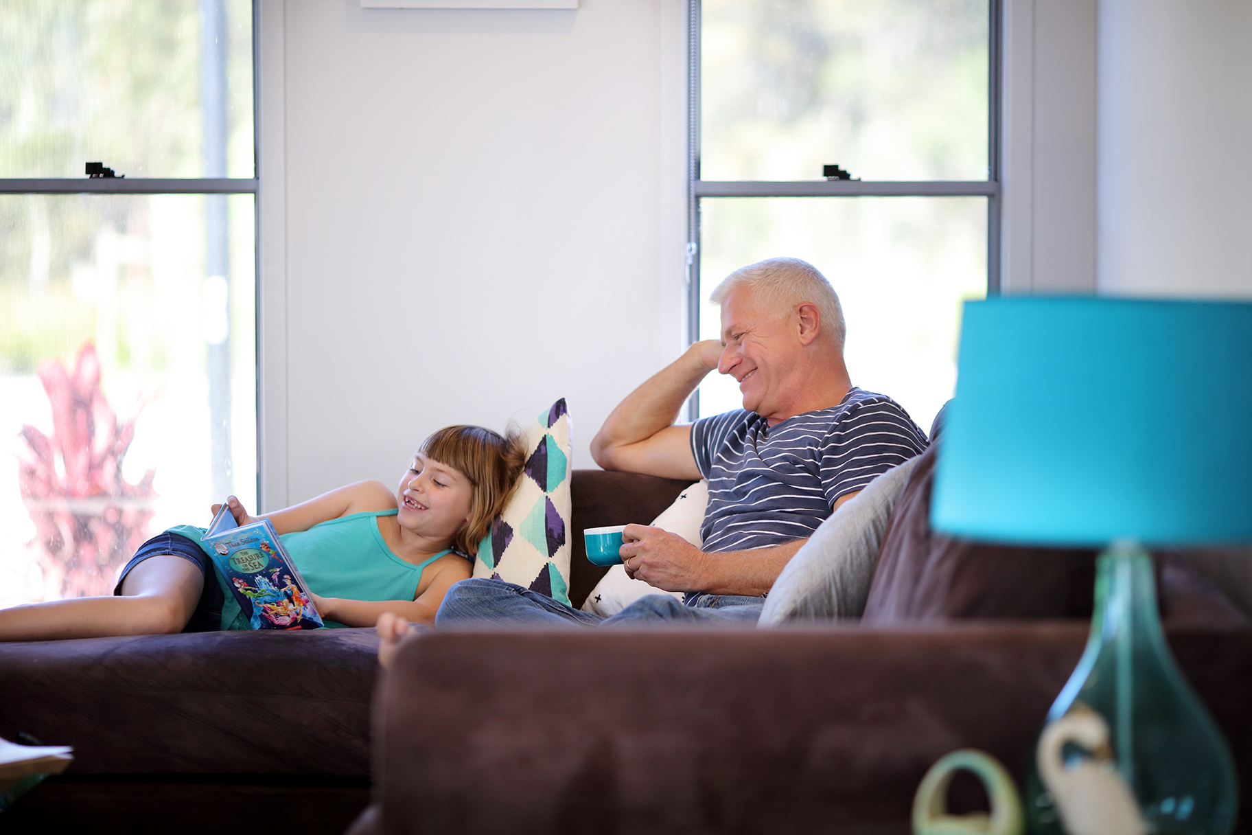 Man drinking tea and young girl reading book on couch