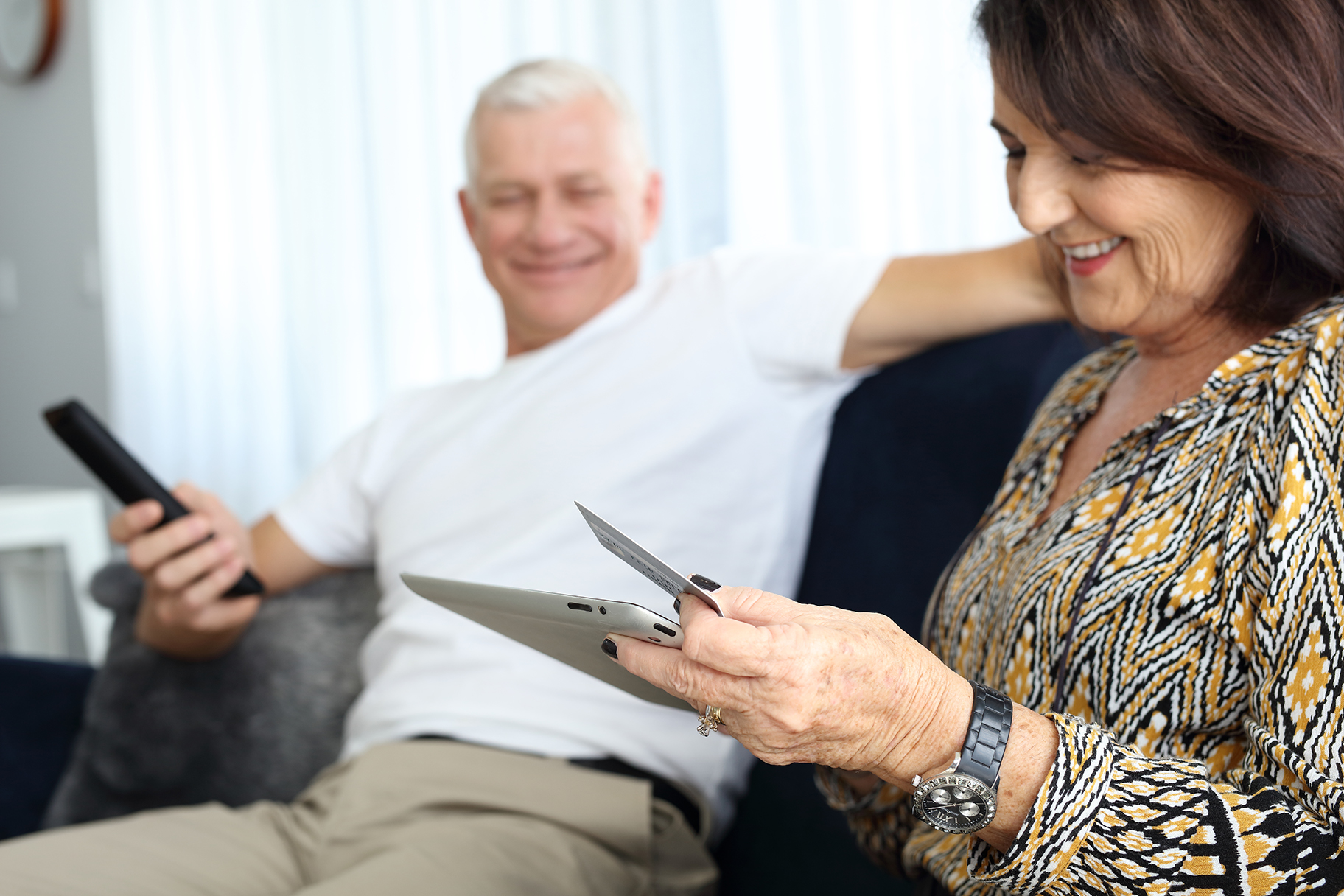 Man holding TV remote woman looking at tablet with credit card on couch