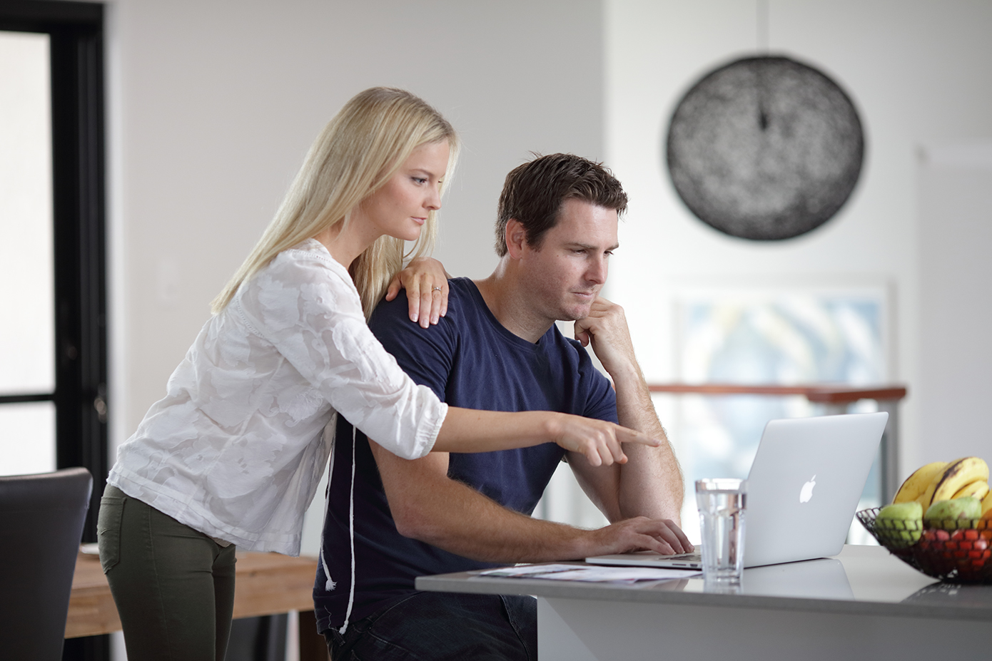 Woman and man looking at laptop computer on residential kitchen bench