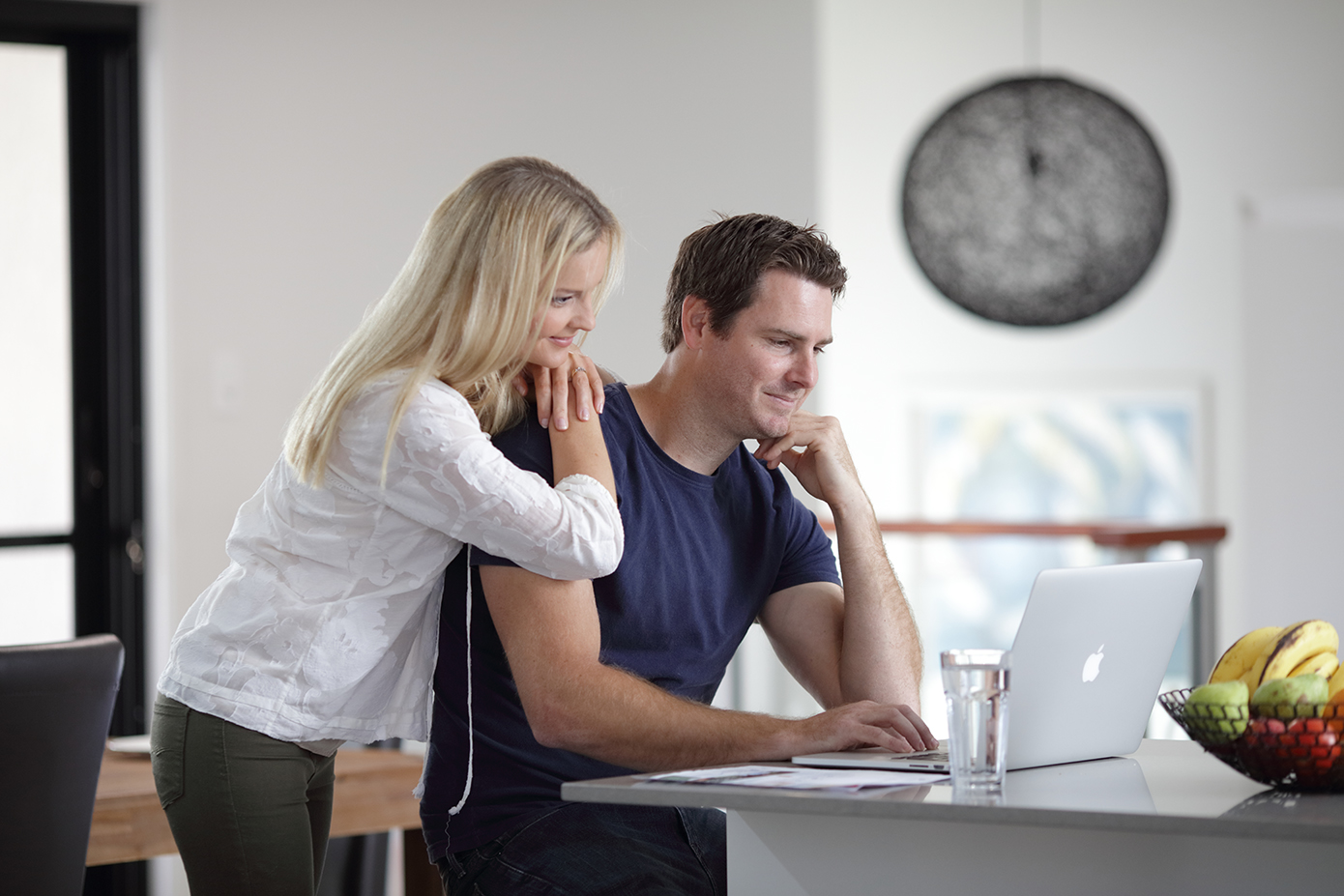 Couple looking at laptop computer on residential kitchen bench