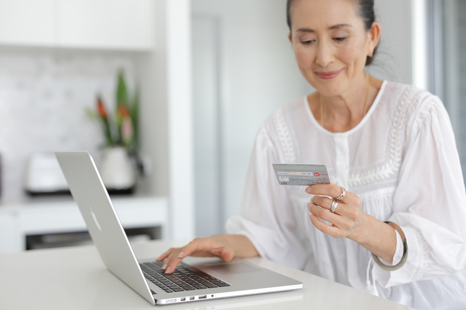 Woman pay bill with credit card on laptop computer in kitchen