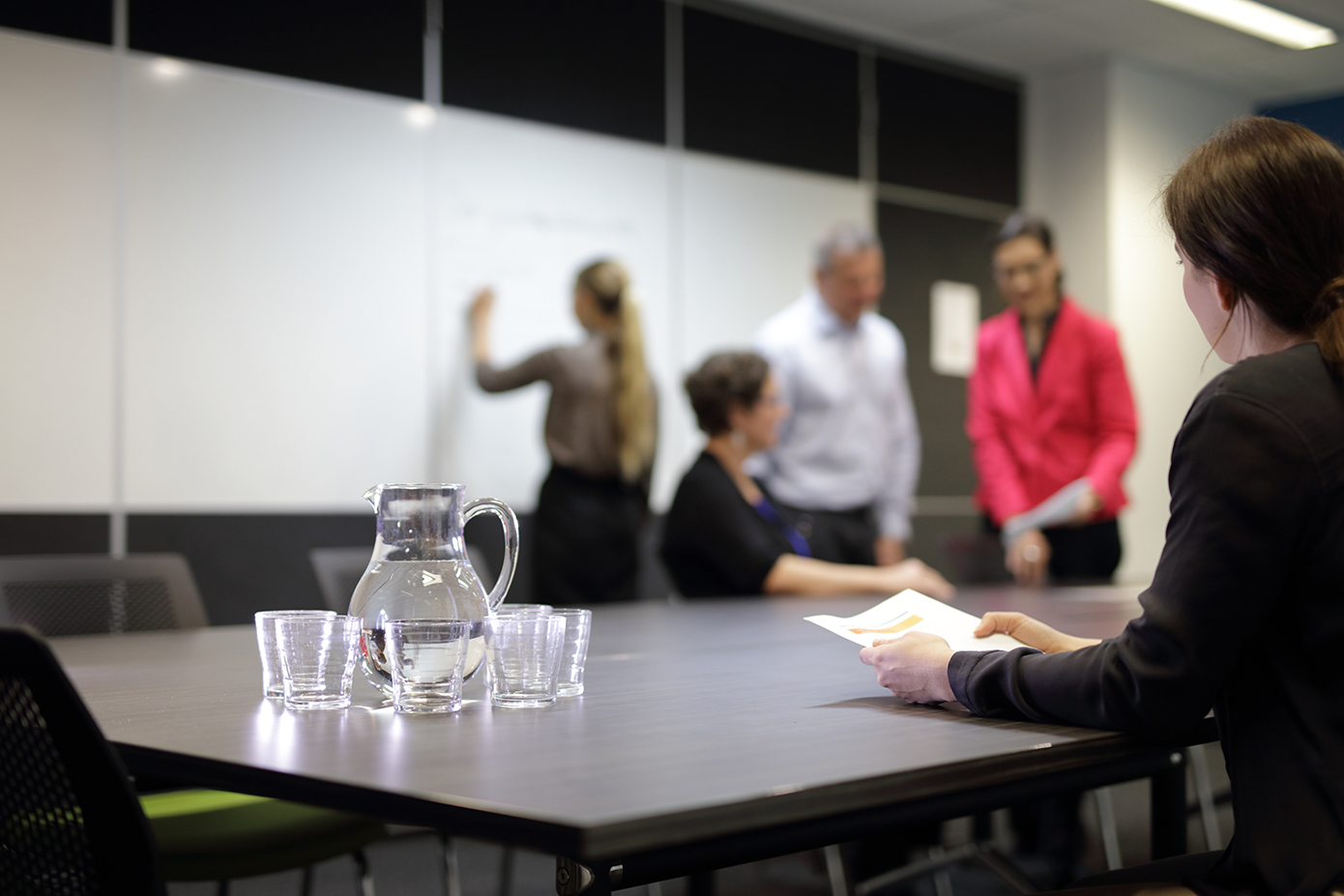 Business people in meeting room with jug of water