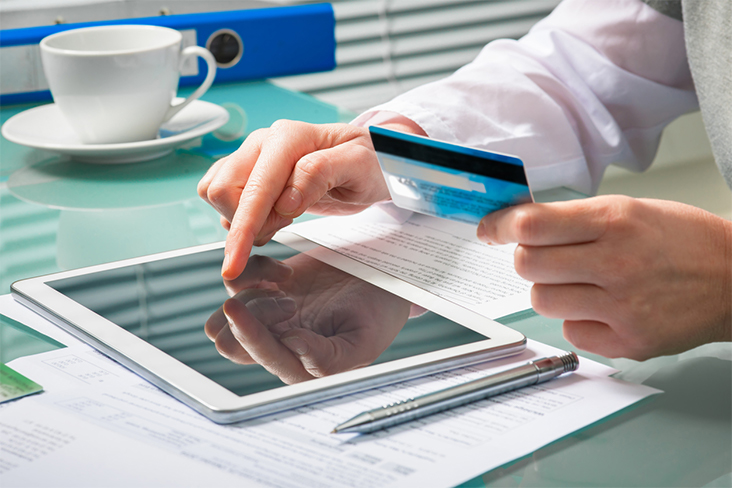 Business person paying online with credit card and iPad