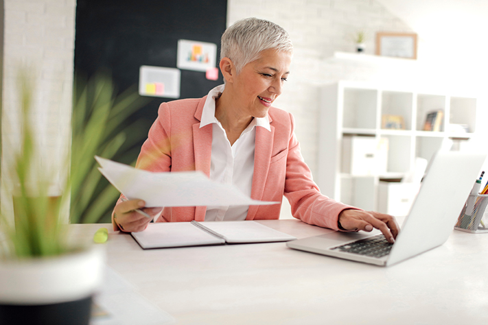 Business woman in office looking at laptop holding paperwork