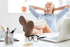 Female office working relaxing with feet on desk