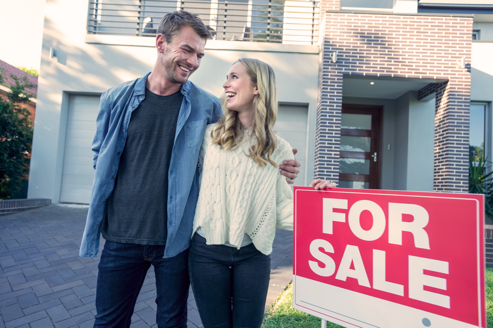Couple standing in front home for sale