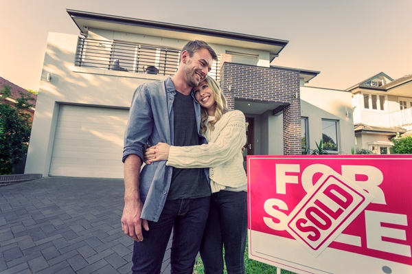Couple standing in front of a new home with Sold sign
