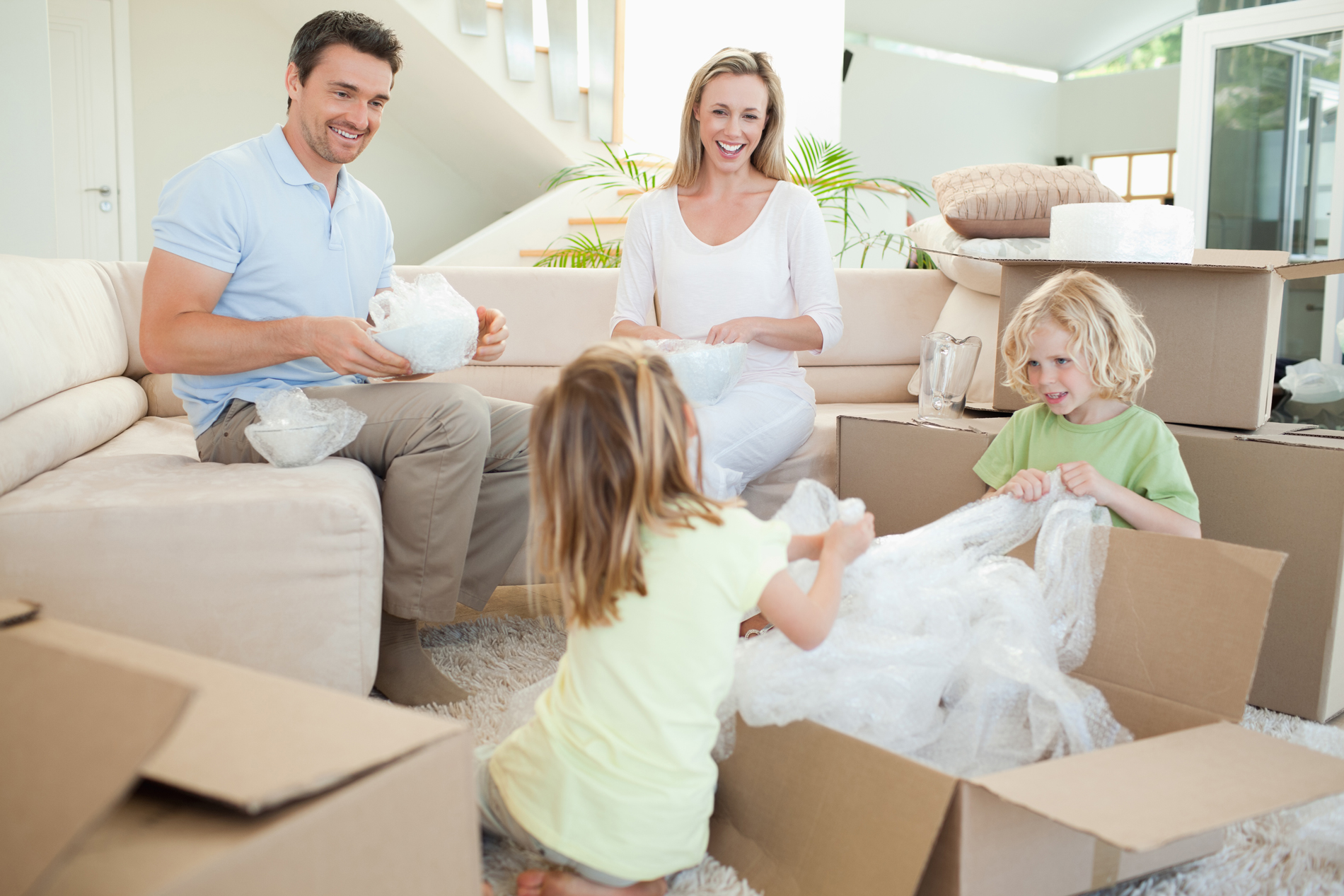 Family unpacking boxes in lounge