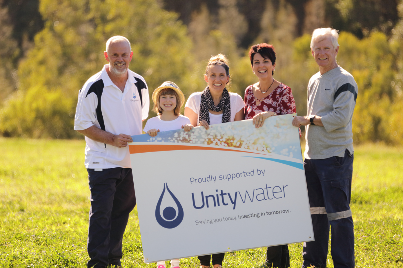 Group of people holding Unitywater sponsorship sign