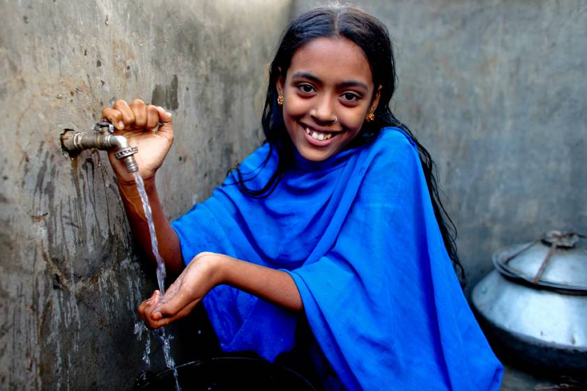 A girl washes her hands from a new tap in Bangladesh.