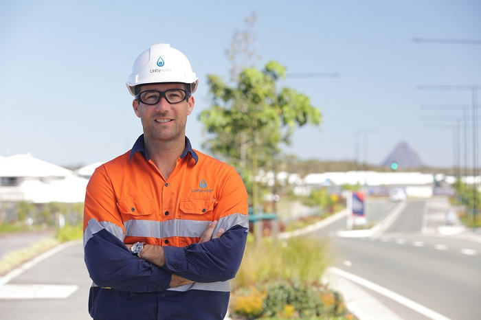 Development services officer standing in front of residential development