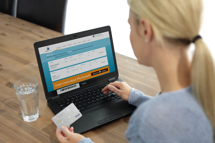 Woman holding credit card while on computer looking at my account