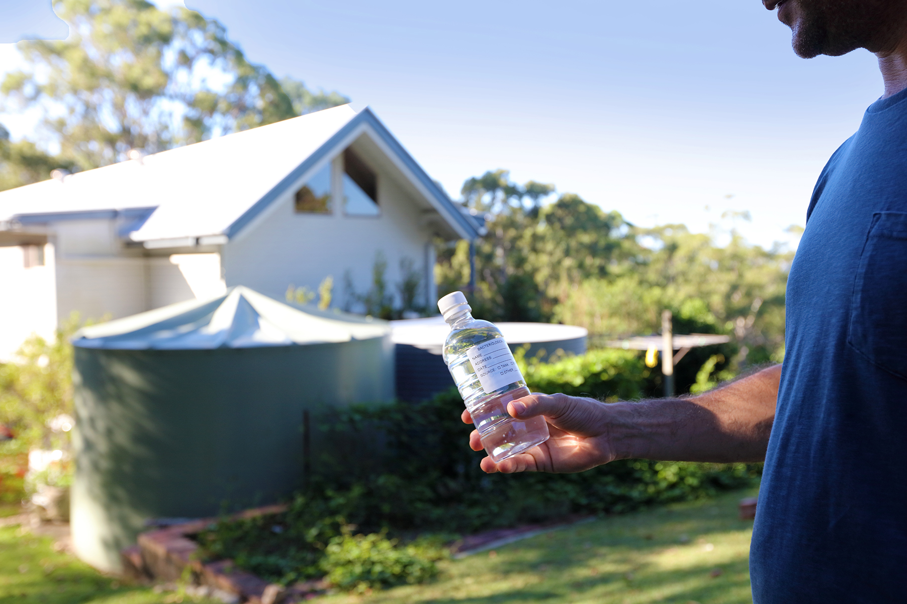 Man collecting water from residential tank for water testing