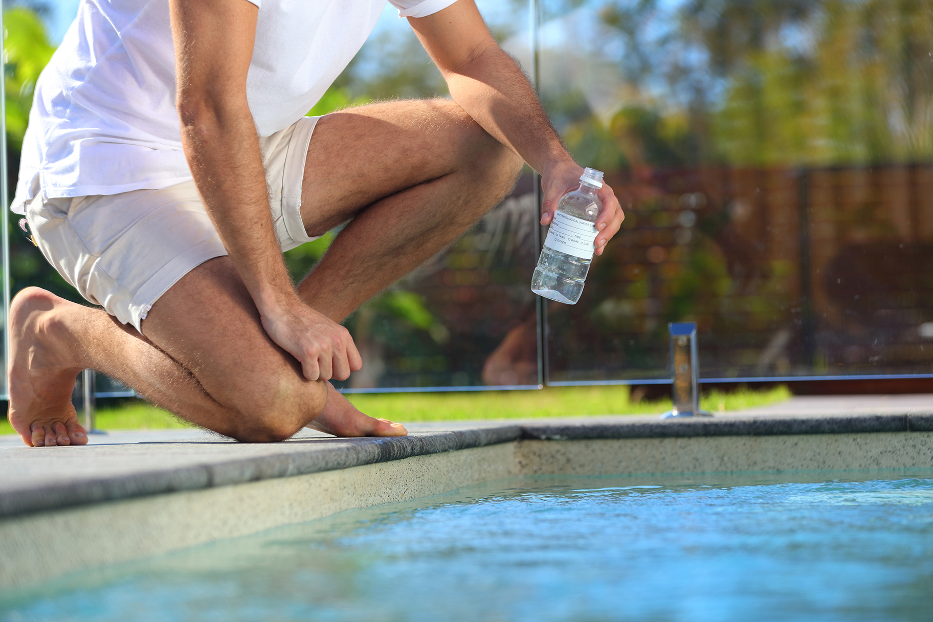 Man filling water testing bottle with water from swimming pool