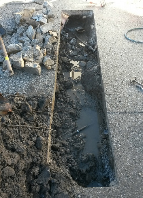 Concealed leak being repaired under concrete driveway