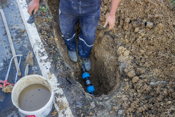 Plumber fixing water leak in pipe under ground