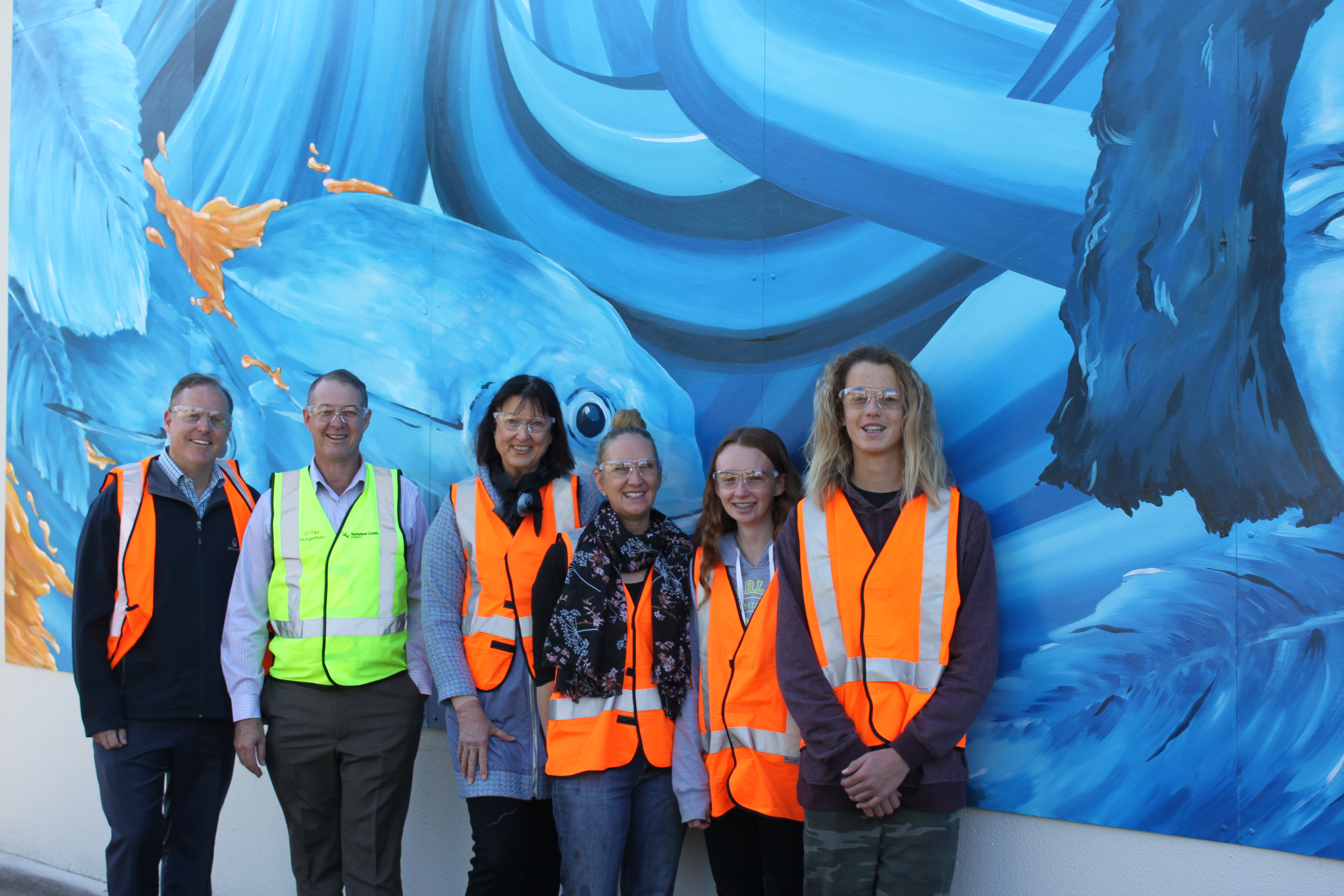 Fishermans Rd pump station mural. Unitywater Community Relations Manager Chris Jones, Councillor Ted Hungerford, Councillor Jenny McKay, Barb Sinclair, and students involved in the project Tallulah Veal-Sinclair and Jye Parkinson
