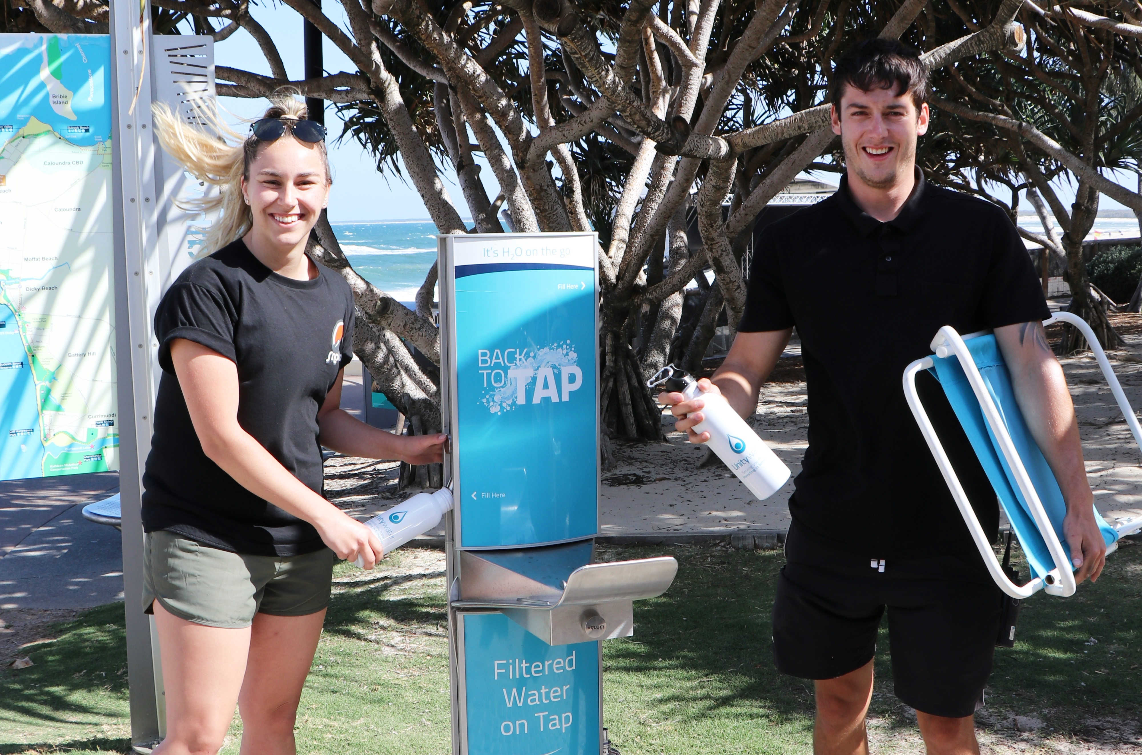 Sam Beattie and Sam Clothier use the Back to Tap refill station at Kings Beach ahead of Caloundra Music Festival.