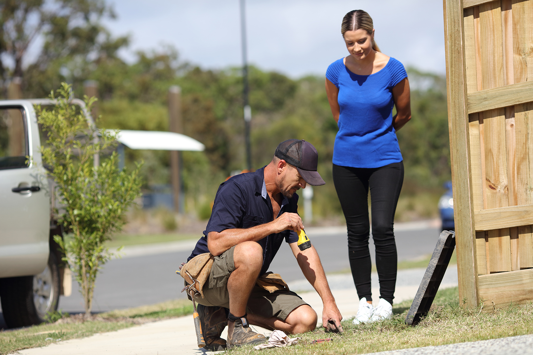 Plumber and woman looking into water meter box in front of residential house