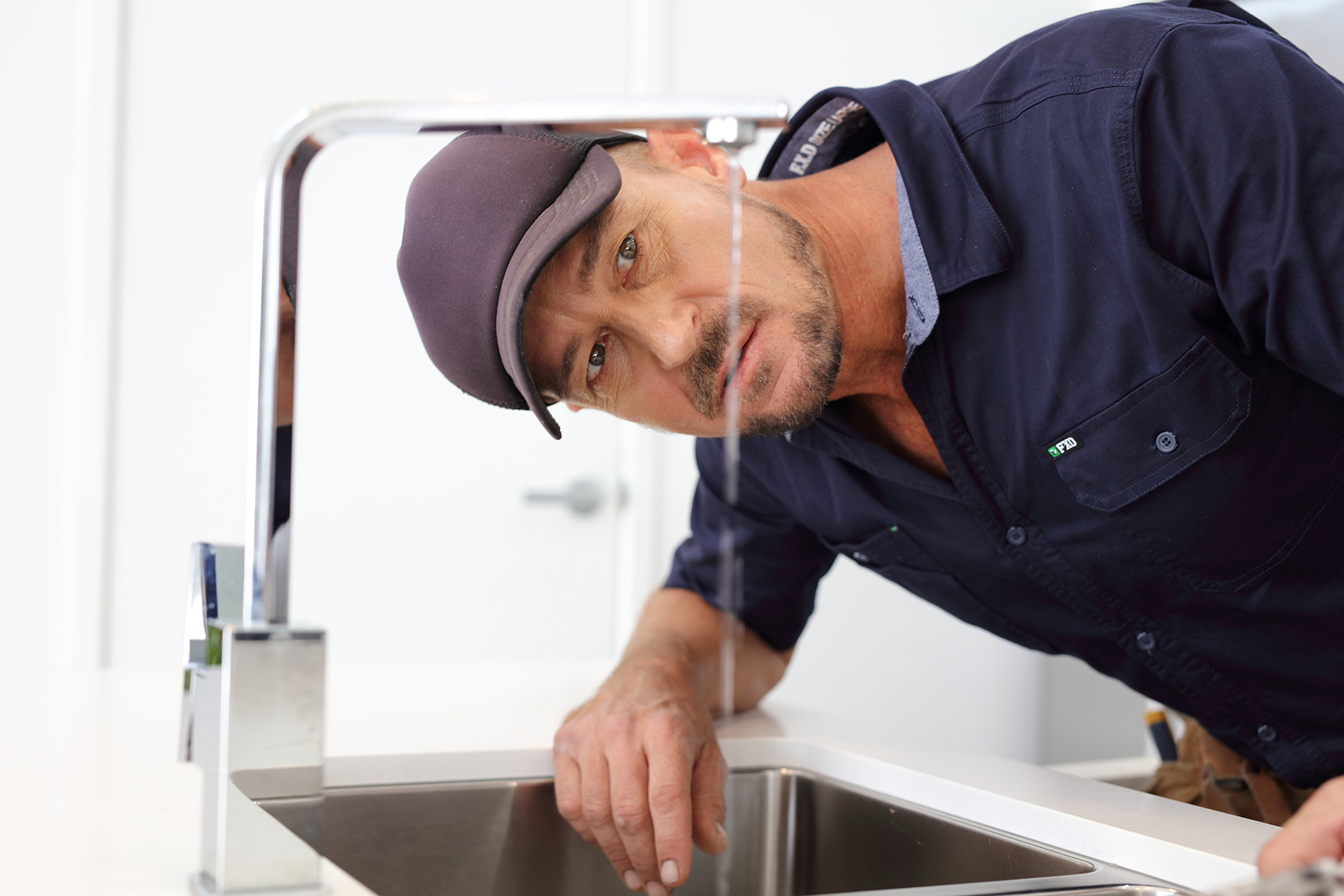 Plumber looking at leaking tap in kitchen