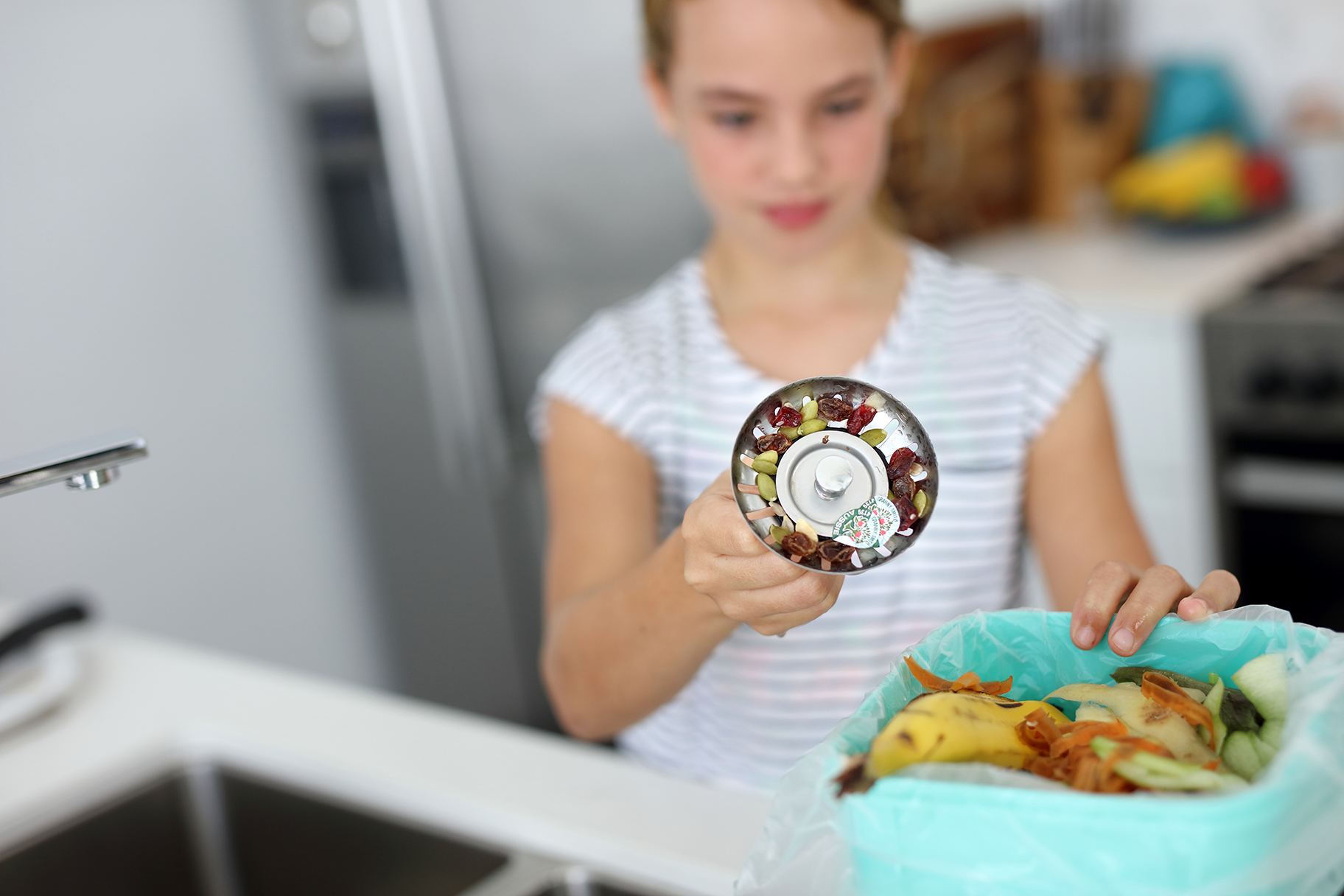 Girl emptying sink strainer full of food scraps into bin on kitchen bench