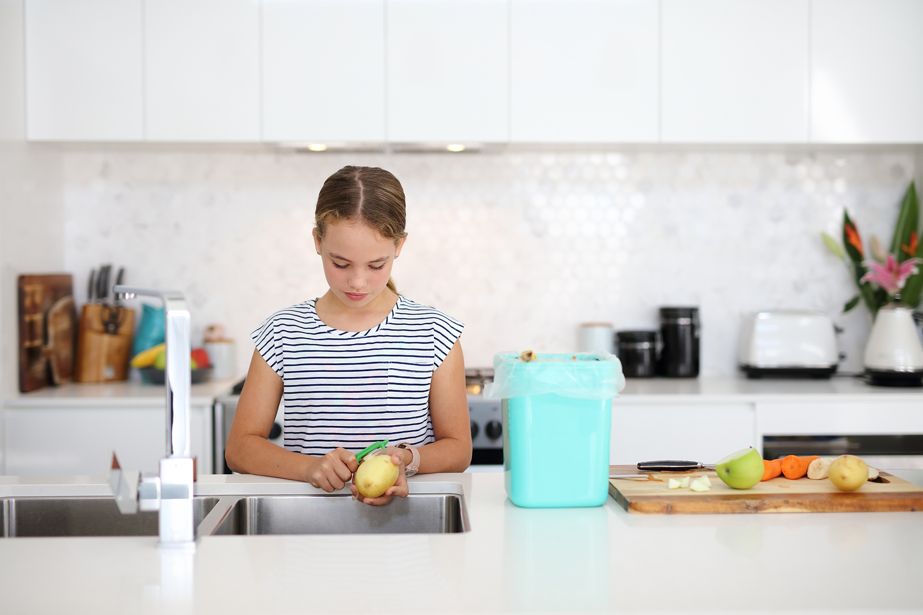 Girl peeling potato at kitchen sink with bin on bench beside her
