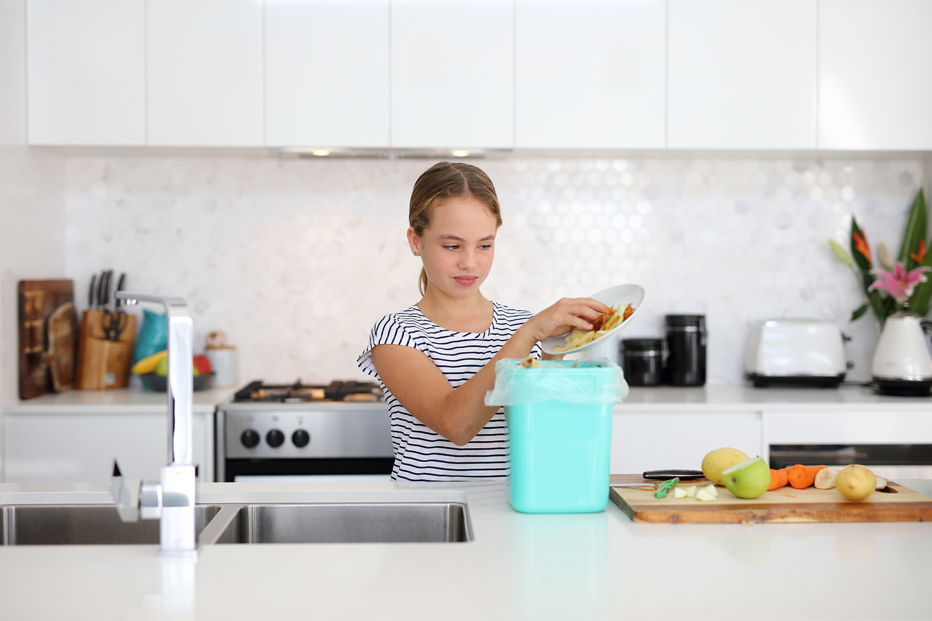Girl putting food scraps from a plate into the compost bin on kitchen bench