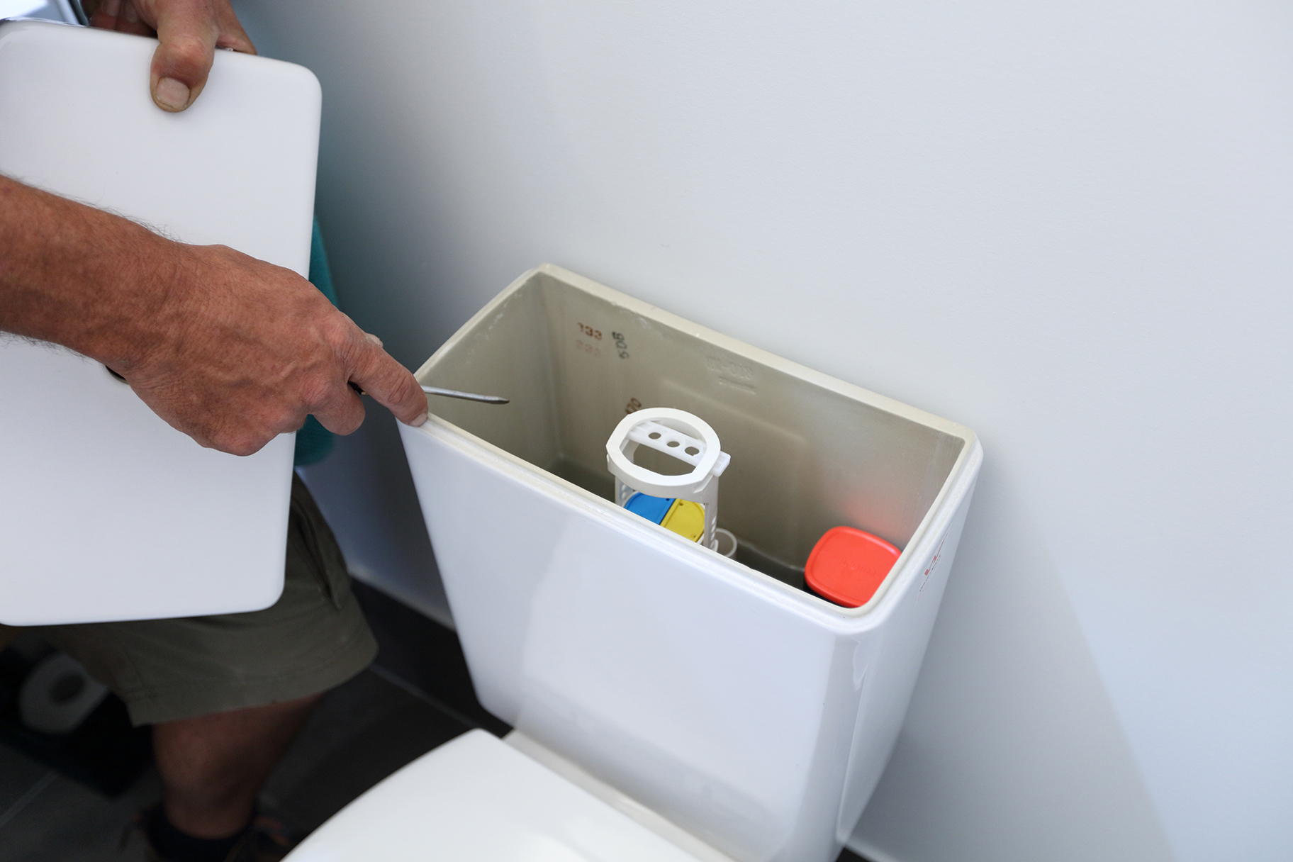 Plumber checking toilet cistern
