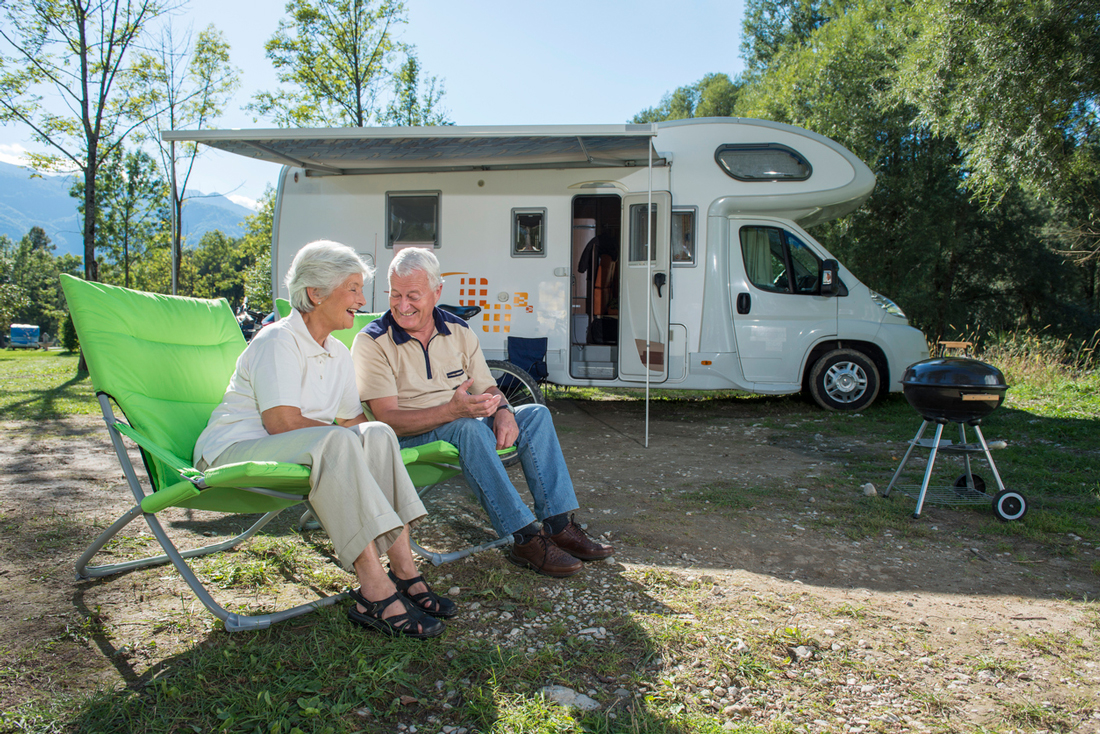 Senior couple camping with camper van