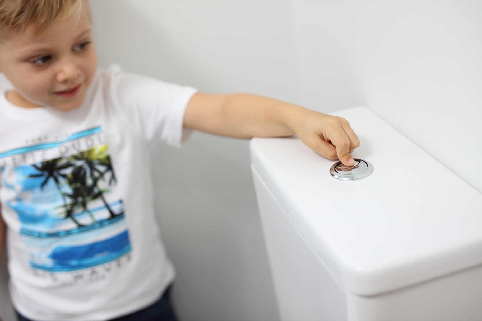 Young boy flushing toilet in bathroom of residential house