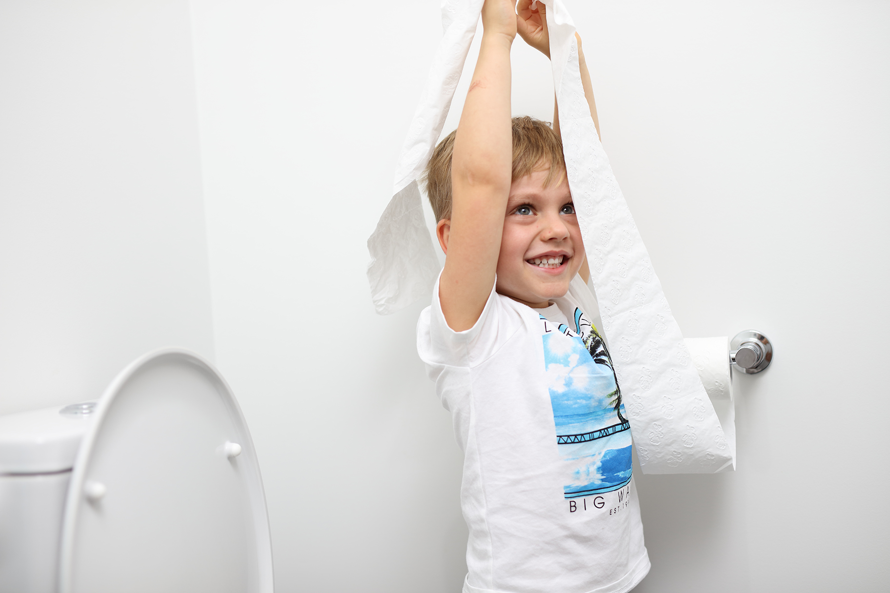 Young boy playing with toilet paper in bathroom of residential house