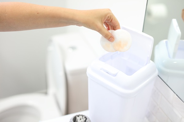 Woman putting round cotton pads into bathroom bin next to toilet