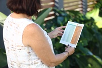 Woman looking at Unitywater Tree Planting Guide in residential garden