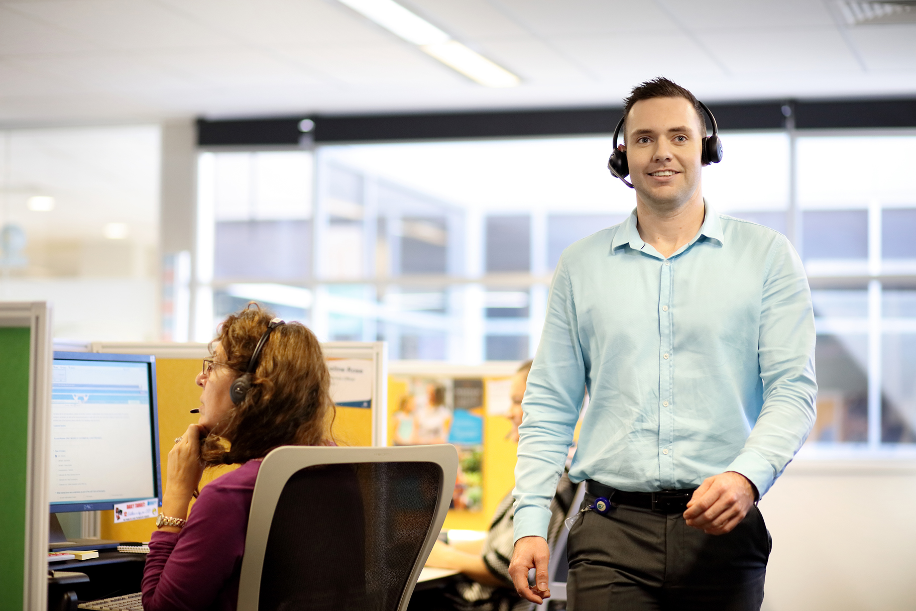 Man wearing headphones working in contact call centre