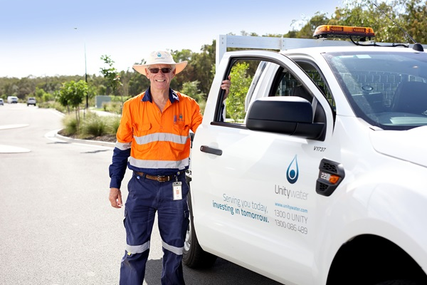 Male Field Crew staff member standing next to Unitywater utility vehicle
