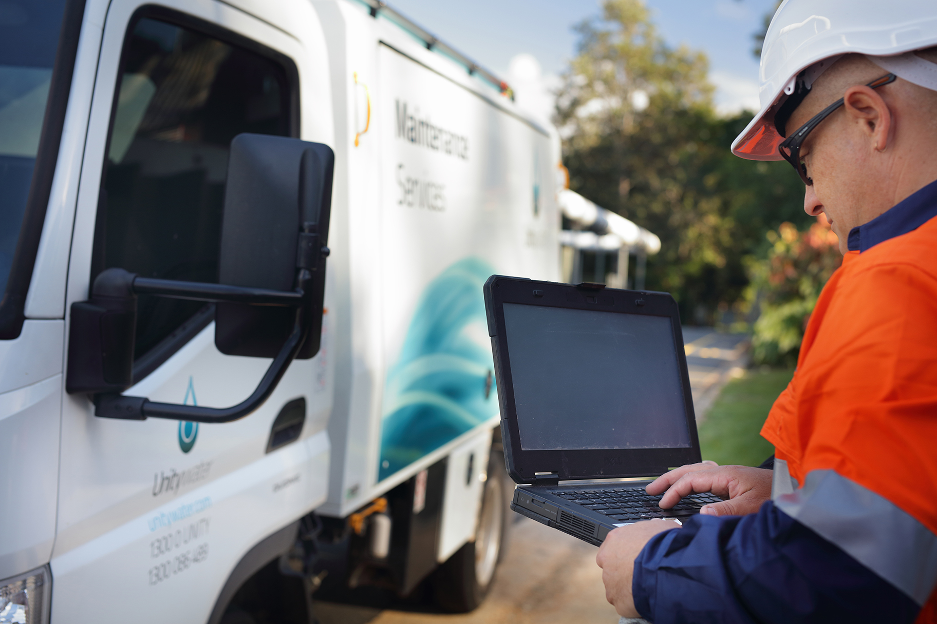 Man looking at laptop computer next to Unitywater Maintenance Services Truck