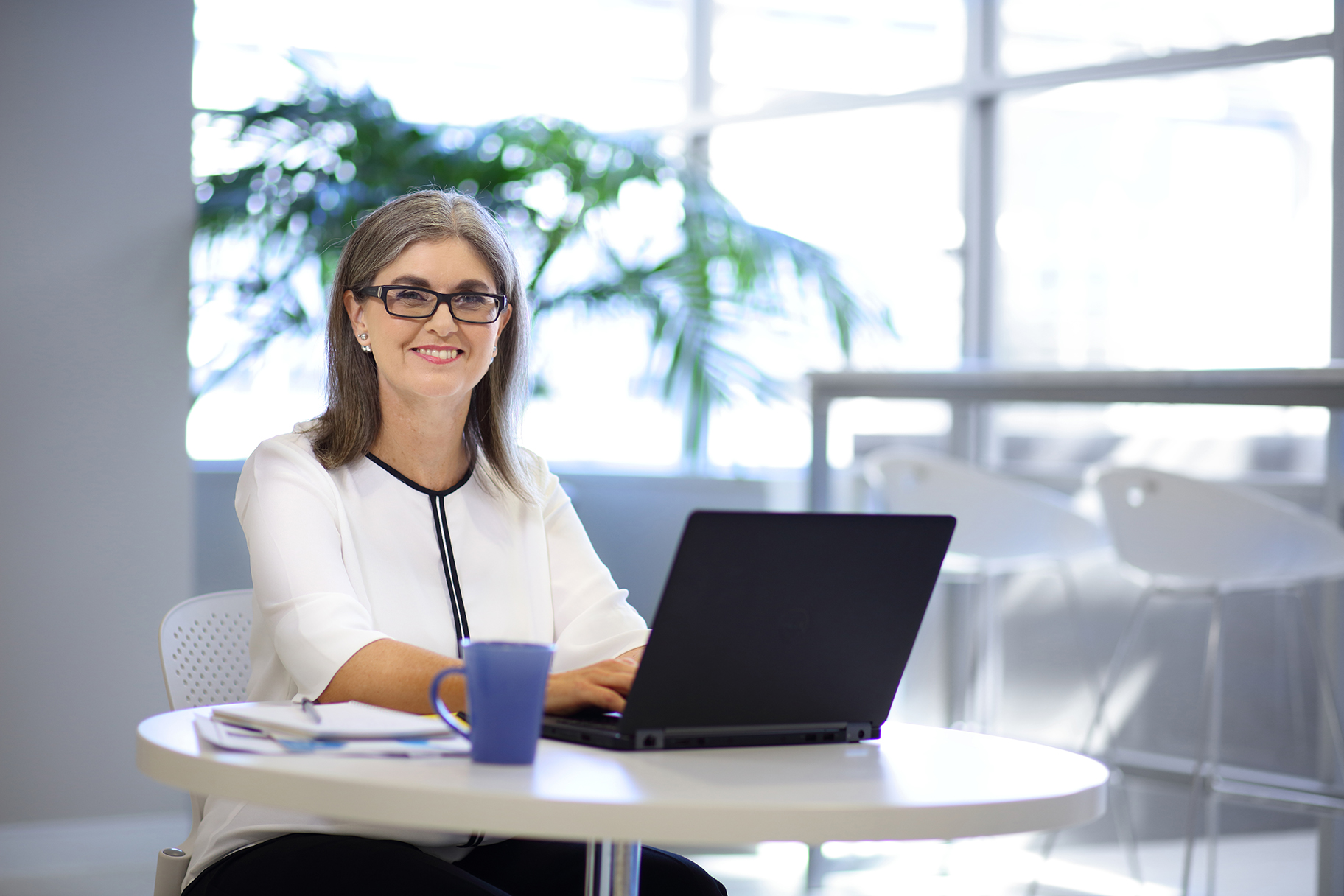 Female staff member typing on laptop computer with coffee in office