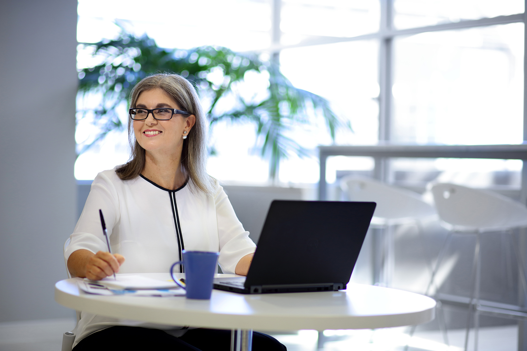 Female staff member writing in office with coffee and laptop computer