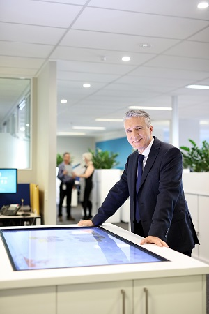 Male staff member operating touch screen in office