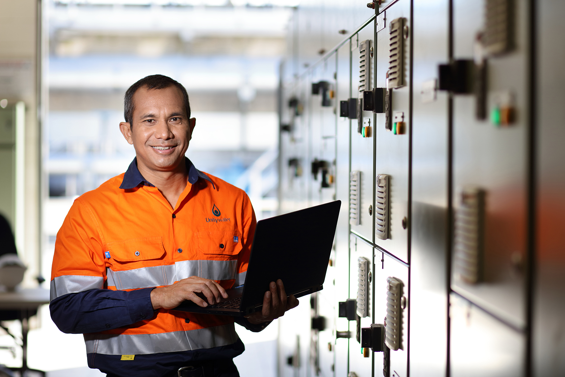 Male staff member holding laptop computer in switchroom at Nambour Sewage Treatment Plant