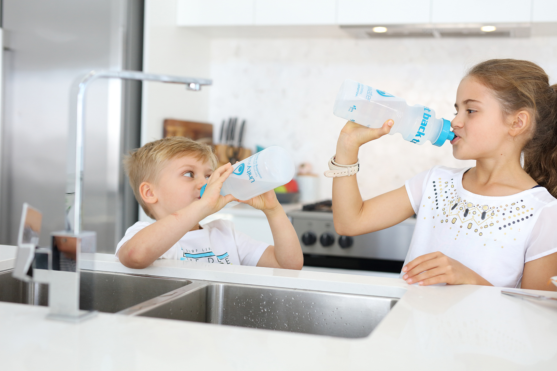 Children drinking from water bottles at kitchen sink