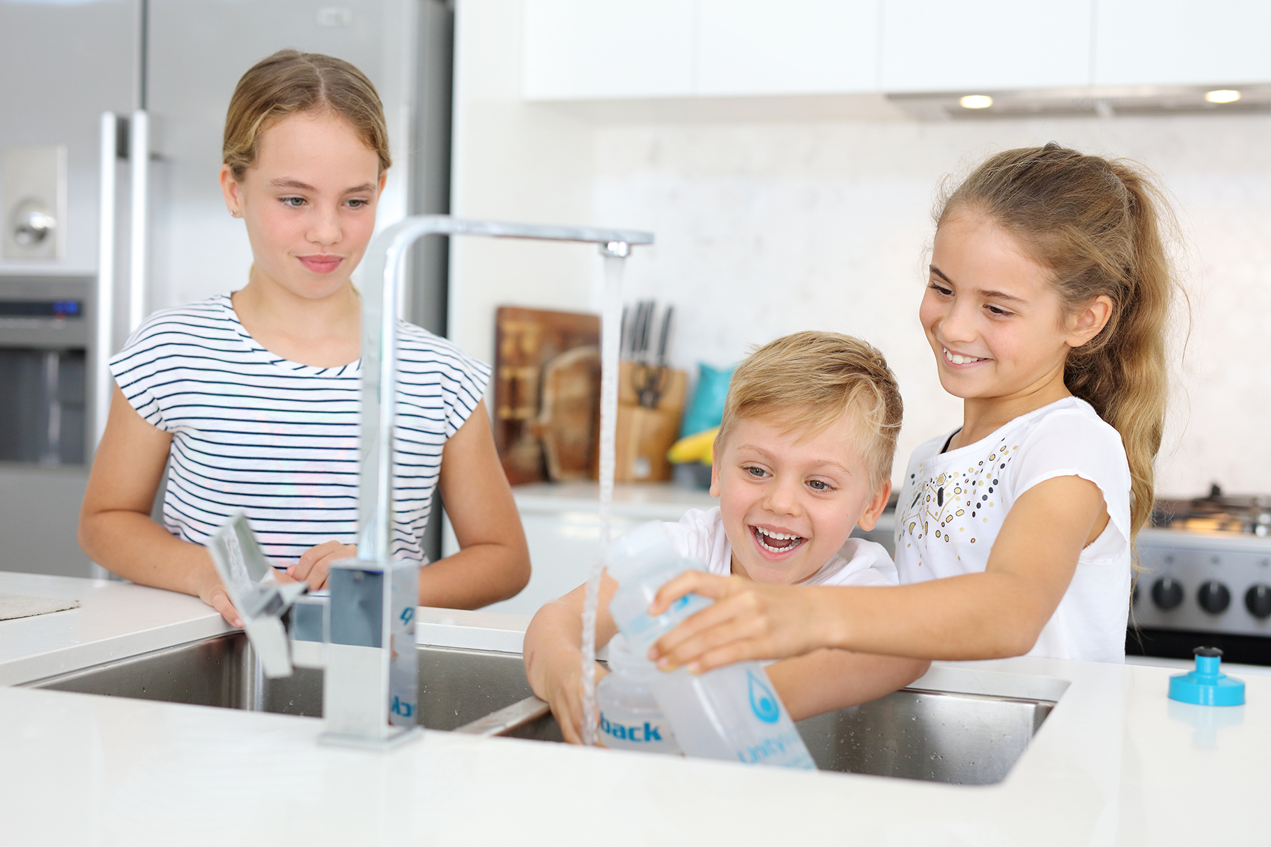 Children filling water bottles at kitchen sink
