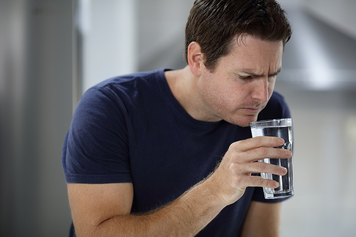Male customer smelling glass of water