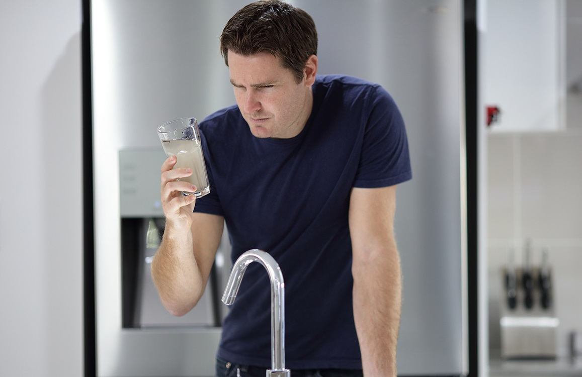 Man looking at dirty water after an outage