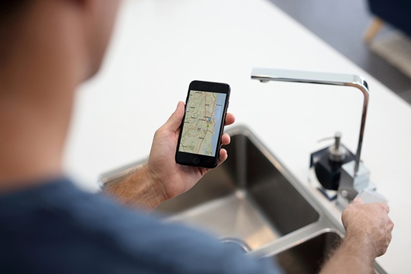 Man looking at phone while checking for water outage at kitchen sink with outages map on screen
